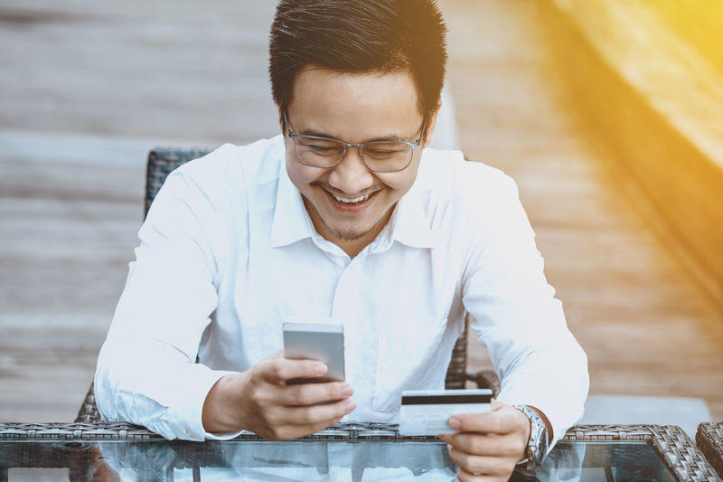 Smiling Young Man Using Mobile Phone While Holding Credit Card At Table