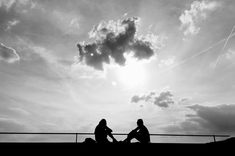 Silhouette People Sitting On Retaining Wall Against Sky