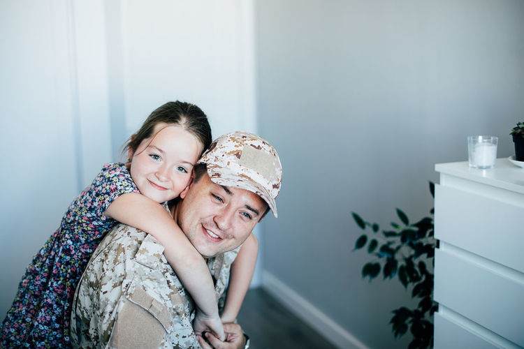 Portrait of girl embracing father in military uniform