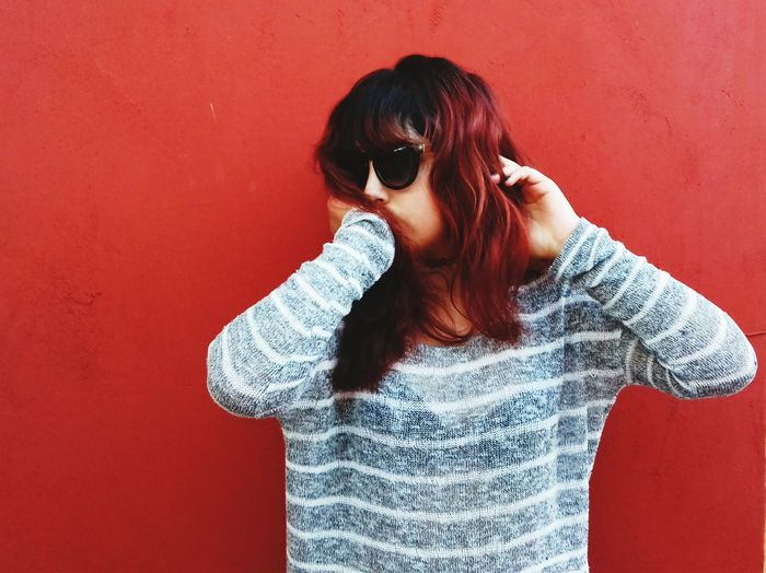Young Woman Wearing Sunglasses Standing Against Red Background