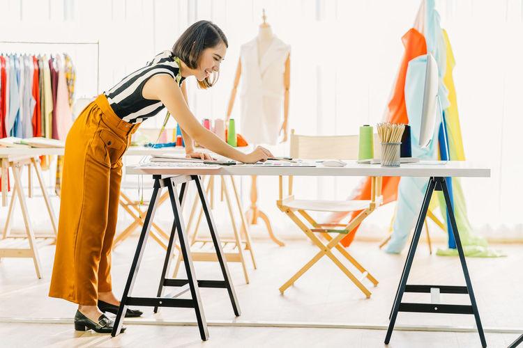 Smiling fashion designer working in boutique
