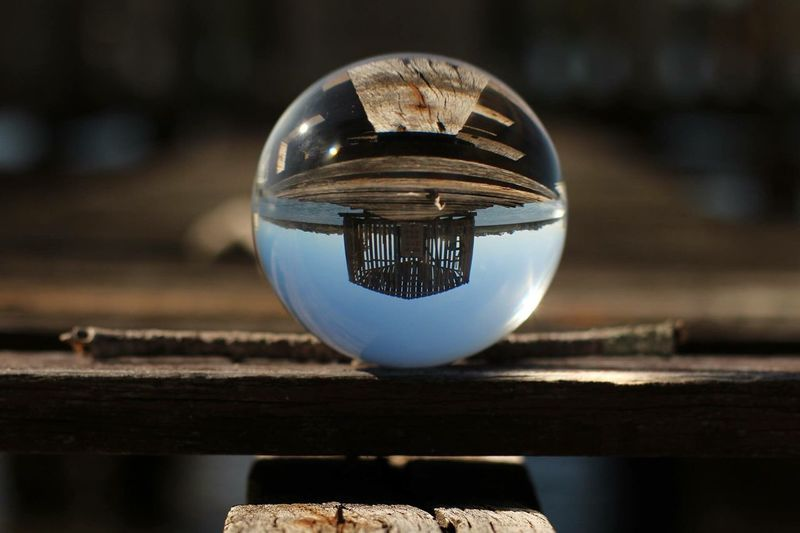 Pier and stilt house reflecting on crystal ball