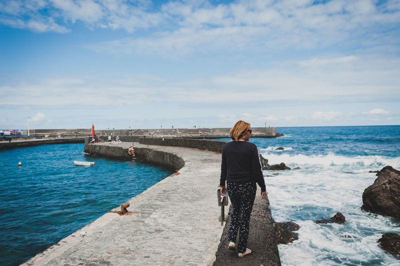 Rear view of woman walking on retaining wall at pier