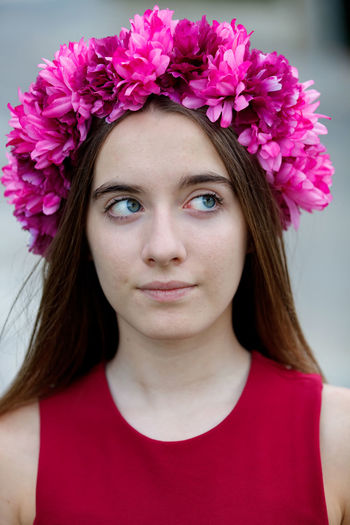 Close-up portrait of beautiful young woman with pink flower