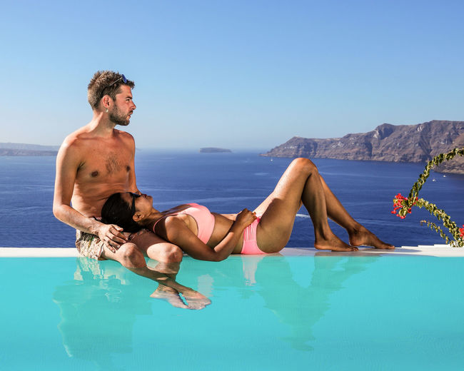 Full length of young couple by infinity pool at sea against clear sky