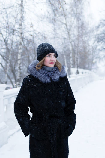 Young woman wearing hat standing against snow during winter
