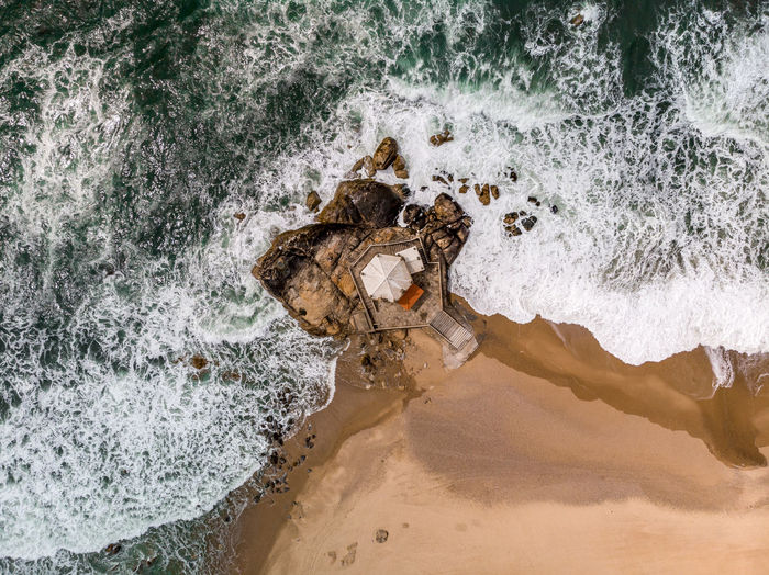 Directly Above Shot Of Waves Rushing On Shore At Beach