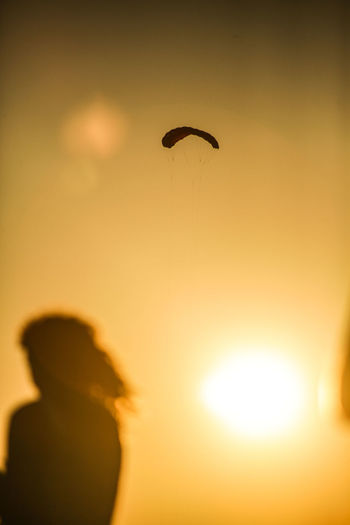 Low angle view of silhouette boy flying against sky during sunset