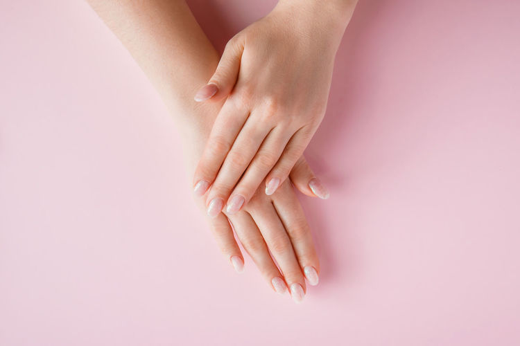 Close-up of woman hand on pink background
