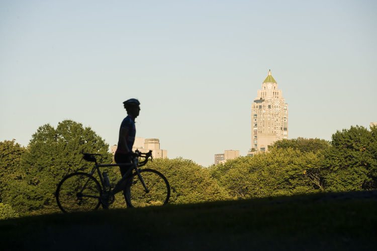 Man riding bicycle by building against sky