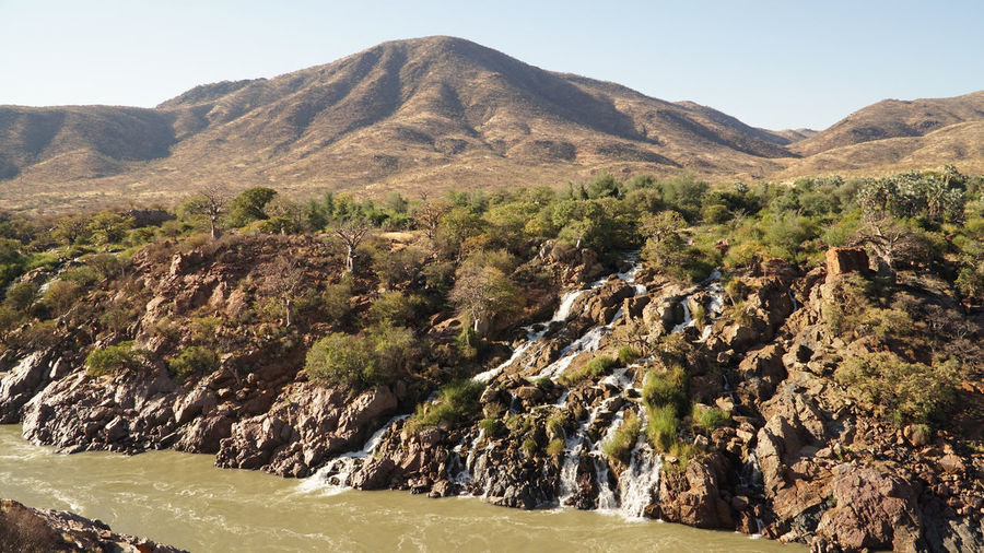 Scenic view of river flowing on arid land against sky