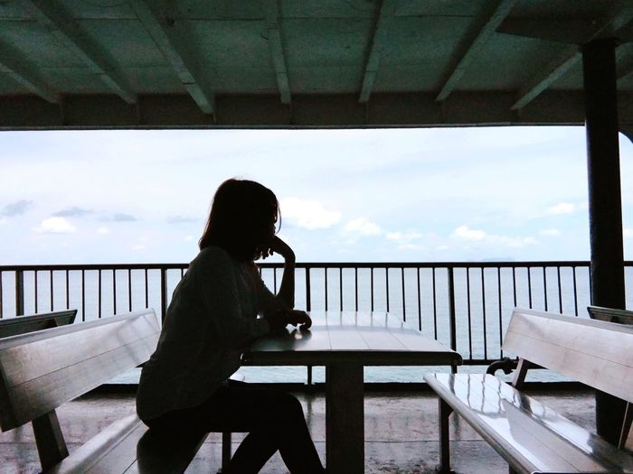 Silhouette woman sitting at table against sky