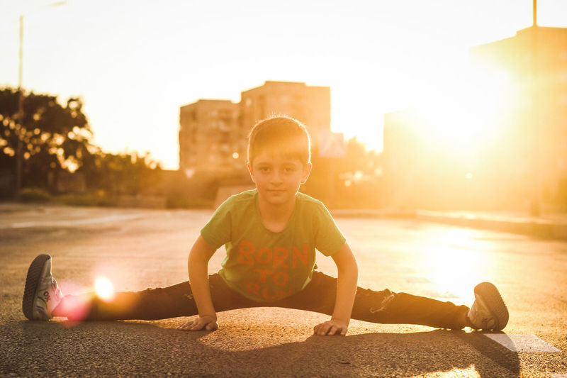 Portrait of boy stretching legs in city against sky during sunset