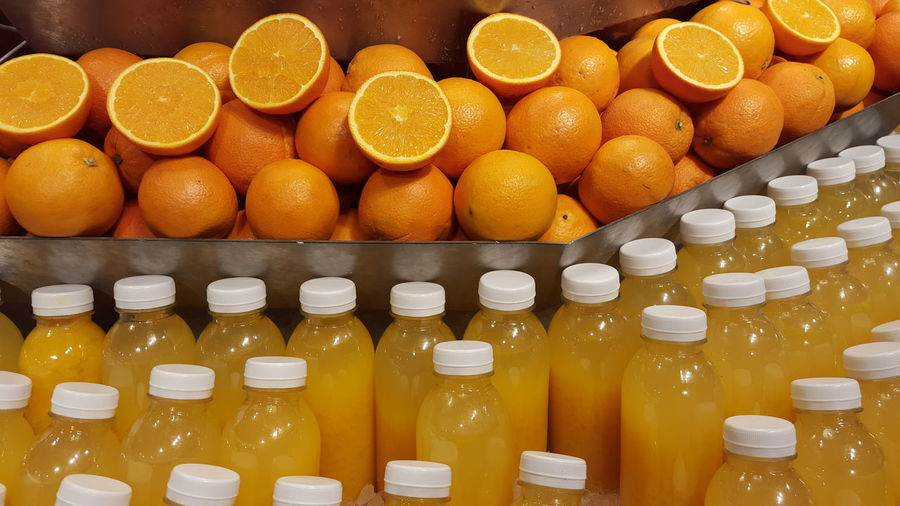 High angle view of fresh oranges and juice bottles at store