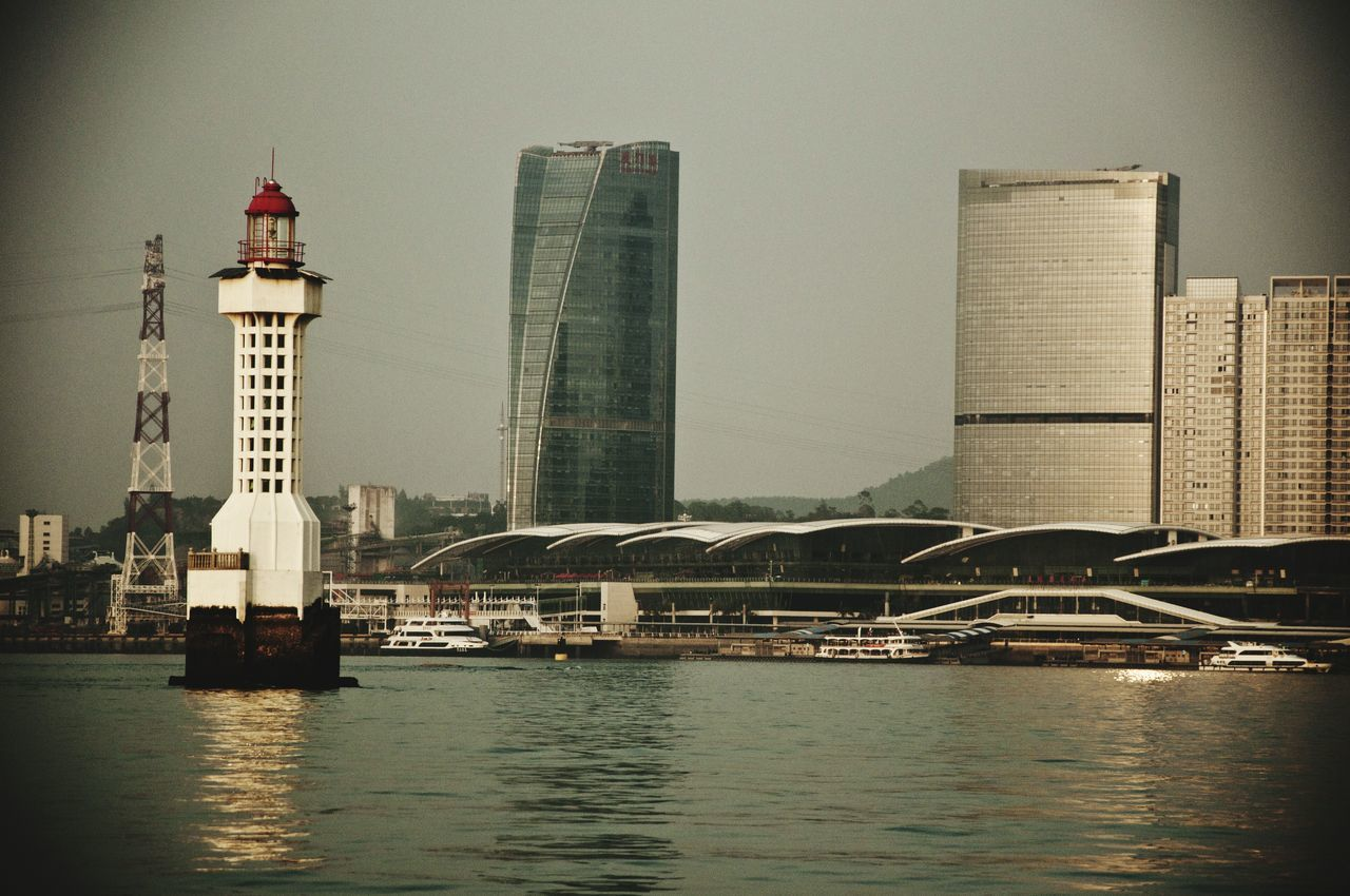 Lighthouse Amidst Sea Against Modern Buildings In City