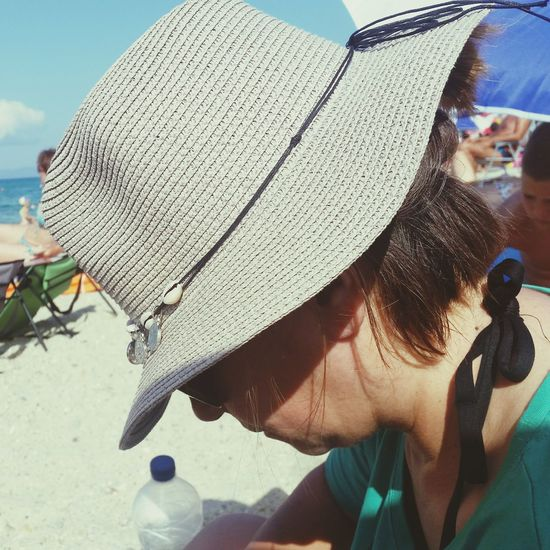Close-up of woman wearing hat at beach