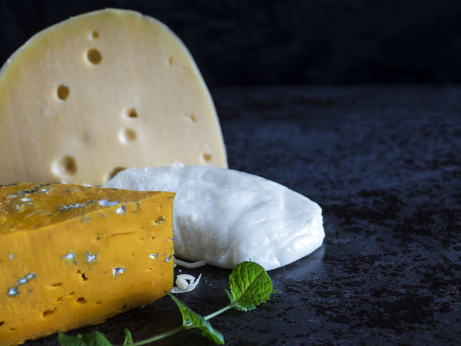 Fresh pieces of cheese (Mozzarella, roquefort, Maasdam) on the stone table Background Black Black Background Cheese Close-up Food France Fresh Freshness Indoors  Italy Maasdam Mint Mozzarella Netherlands No People Pieces Ready-to-eat Roquefort Slate Switzerland Table