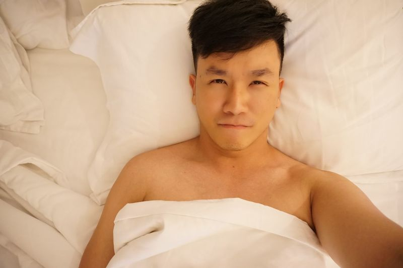 Directly above shot of shirtless man lying on bed