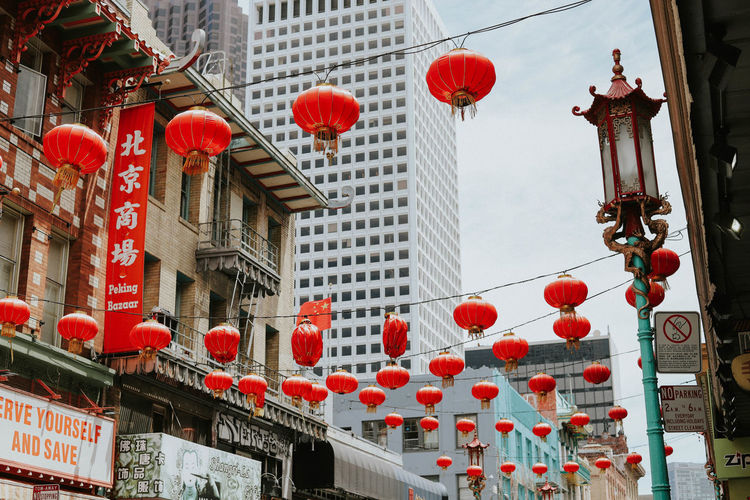 Low angle view of lanterns hanging on street amidst buildings in city