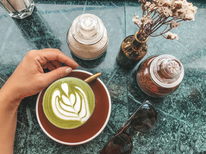 High angle view of matcha latte cup on table