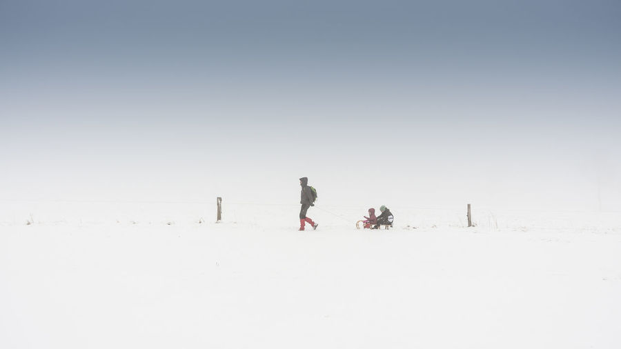 Man Pulling Family On Sled Against Sky