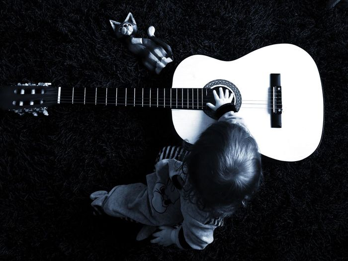 High Angle View Of Child Sitting By Acoustic Guitar On Rug