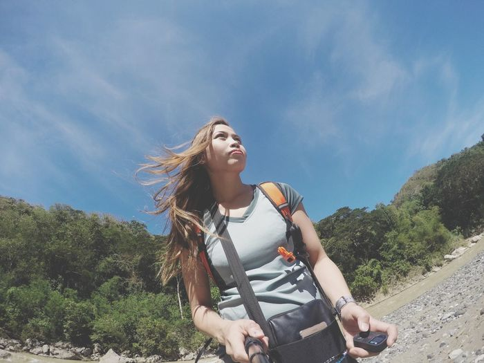 Low angle view of woman with backpack against sky