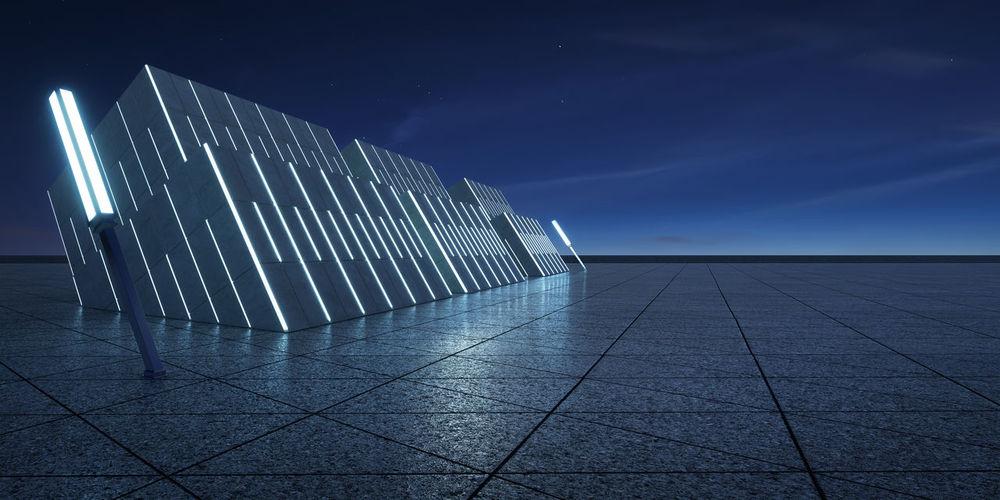 Illuminated footpath against blue sky at night