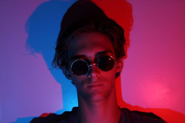 Portrait of young man wearing sunglasses in light against wall