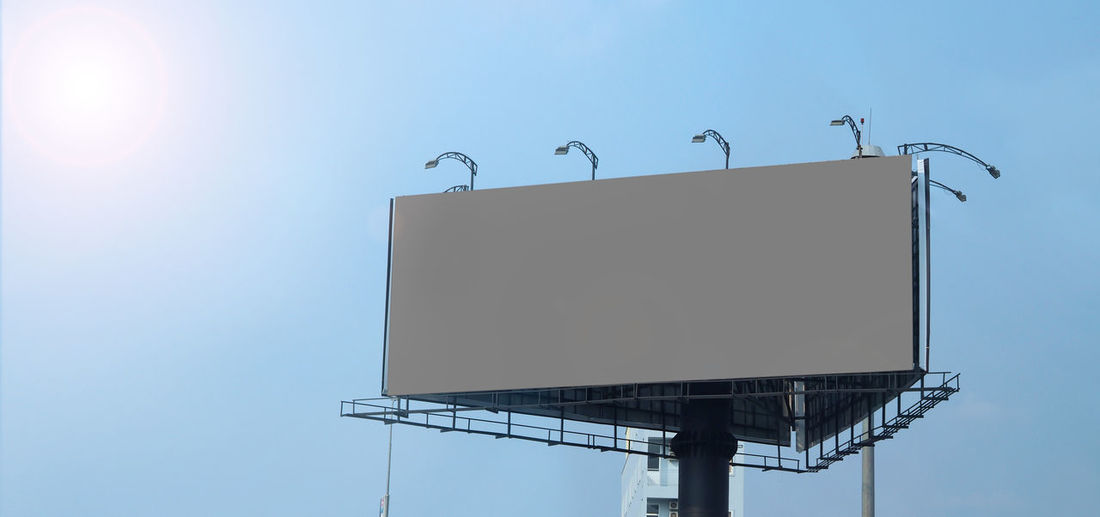 Low angle view of blank billboard against clear sky during sunny day
