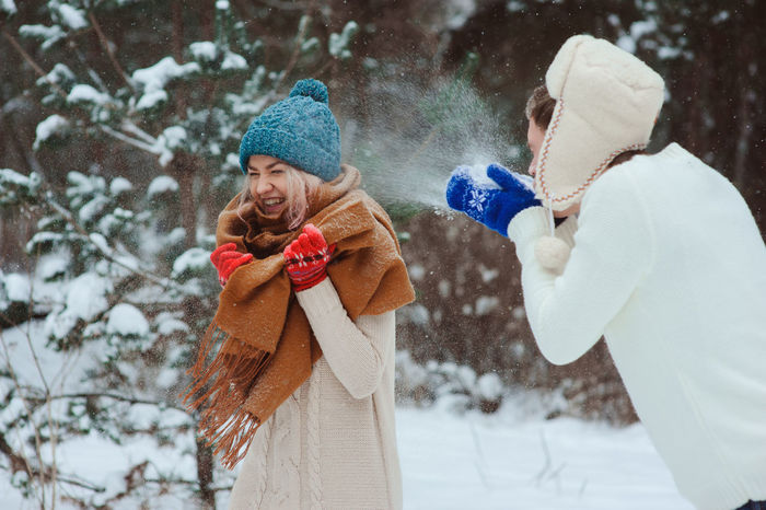 Man and woman enjoying in snow during winter