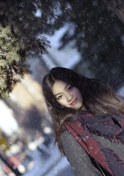 Sunlight Beautiful Woman Close-up Cold Temperature Day Happiness Leisure Activity Lifestyles Looking At Camera Nature One Person Outdoors Portrait Real People Smiling Snow Snowflake Snowing Standing Tree Warm Clothing Weather Winter Young Adult Young Women