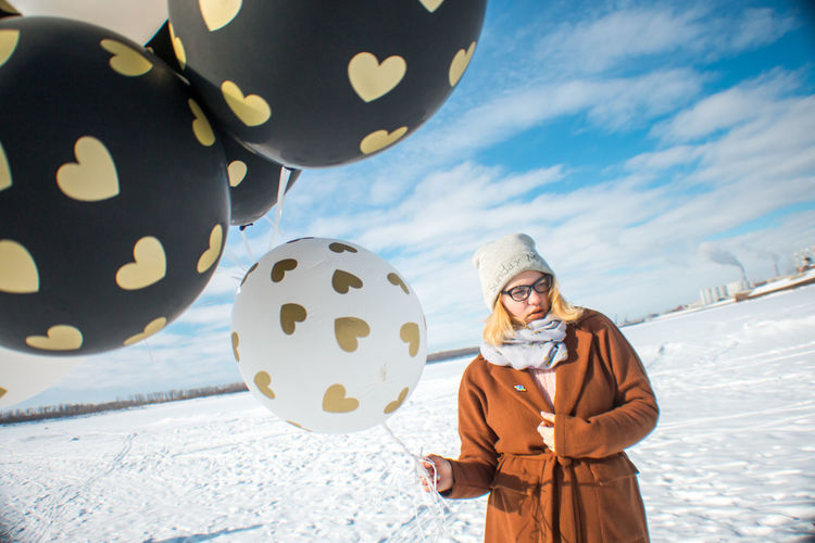 Woman holding balloons on snow covered land