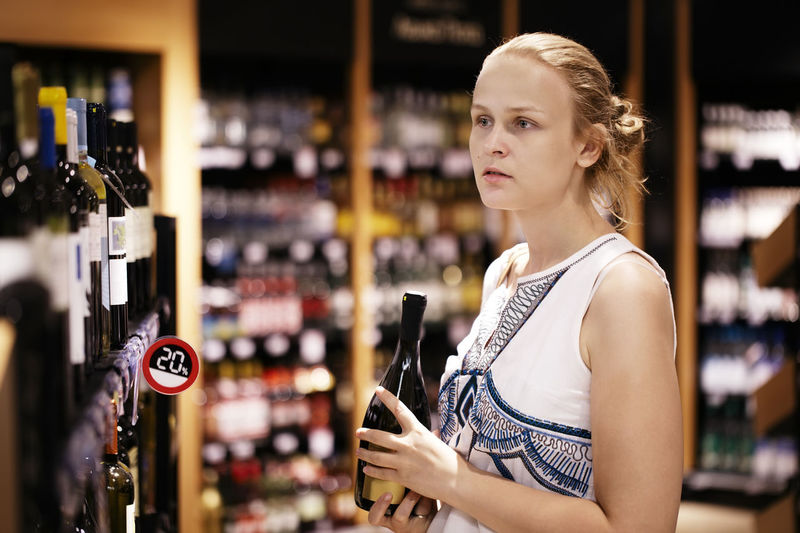 Young woman buying liquor in supermarket