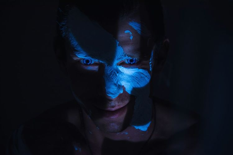 Close-Up Portrait Of Man With Face Paint Against Black Background