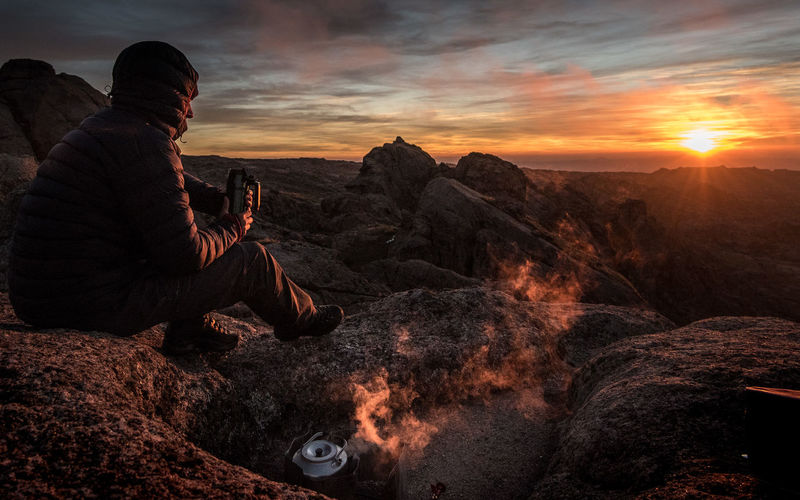 Man sitting on rock against sky during sunset
