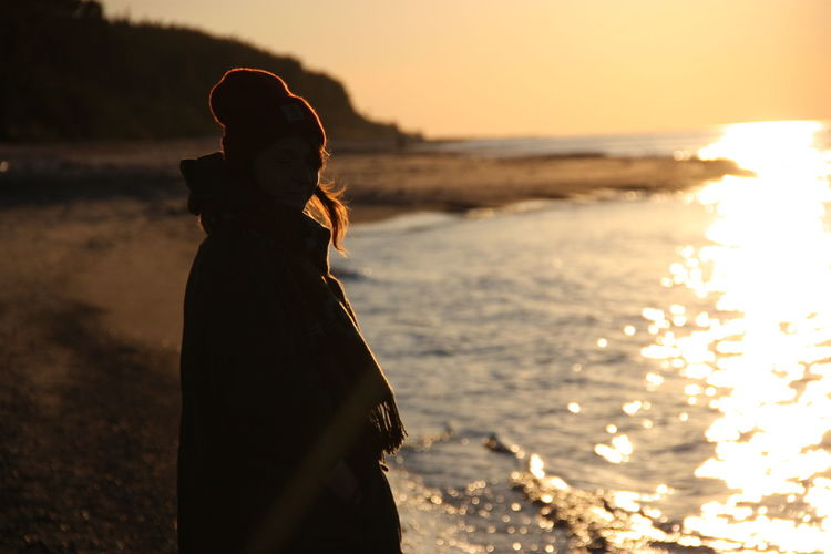 Side View Of Woman Standing By Shore During Sunset