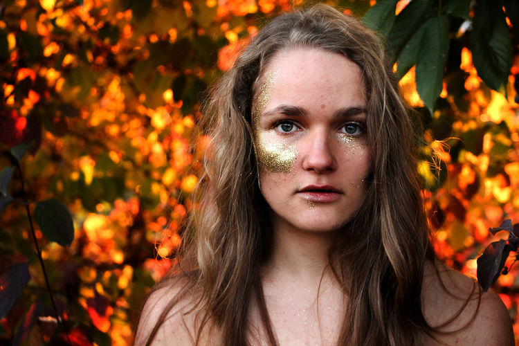 Close-up portrait of young woman with glitter make-up by trees