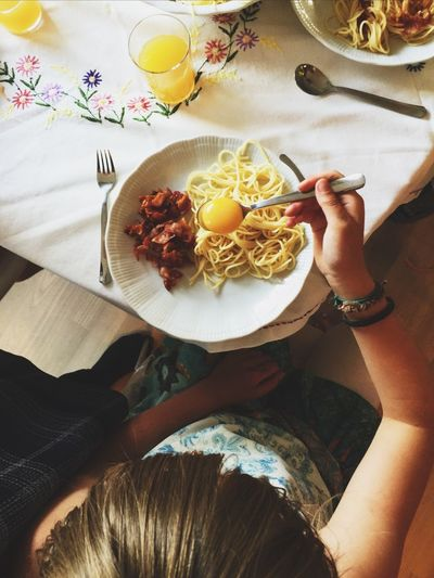 Directly above shot of person with egg yolk in spoon over pasta at home