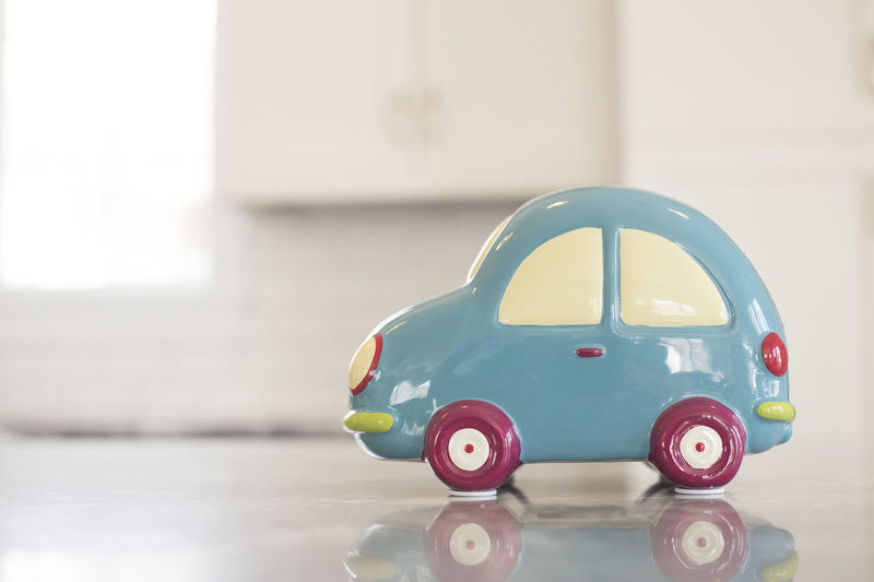 A toy car piggy bank on an obscure background. Horizontal image with space for copy. Bank Banner Car Cars Ceramic Copy Space Horizon Over Water Money Saving Concept Nobody Piggy Bank Saving Money Saving Money For Volkswagen