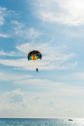 Mid distance view of person parasailing over sea against cloudy sky