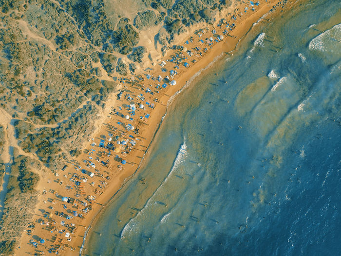 Aerial view of people sitting on a sandy beach. summer colors.