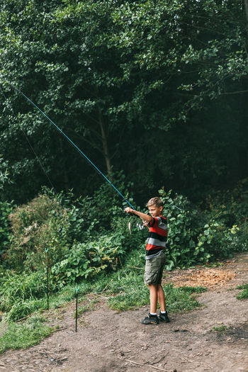 Full length of boy holding fishing rod in forest