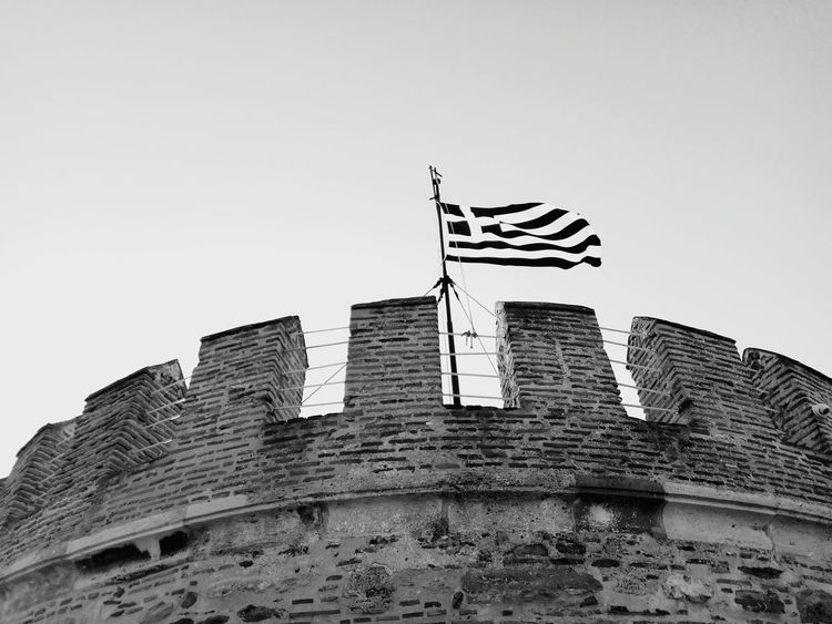 Flag Patriotism Architecture Low Angle View History No People Built Structure Travel Destinations Day Blue Sky Building Exterior OutdoorsClear Sky Brick Wall Greek Thessaloniki Low angle view Clear Sky Skyscraper Stars And Stripes Your Ticket To Europe Greece Black And White Friday