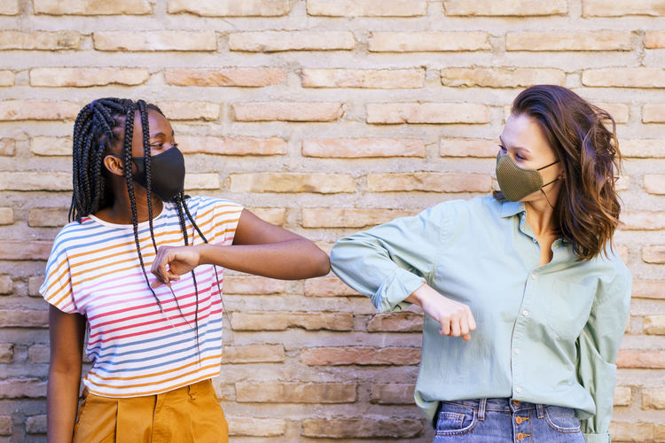 Smiling friends wearing mask doing elbow bump while standing against wall outdoors