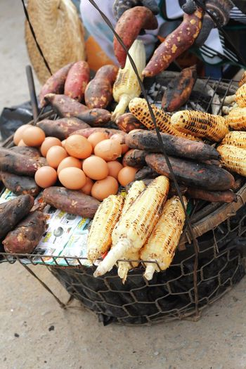 High angle view of corn and sweet potatoes with eggs at street market