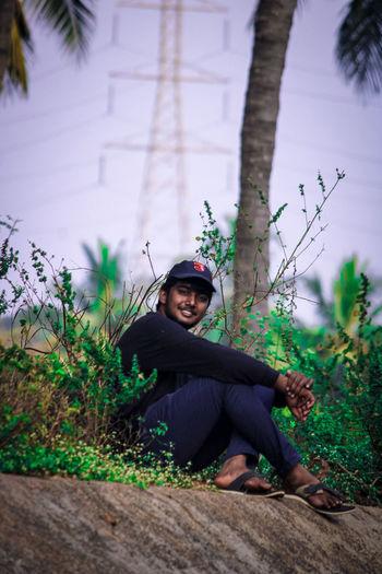 Portrait of man sitting by tree
