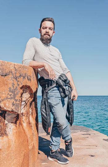One Person Casual Clothing Clear Sky Real People Lifestyles Leisure Activity Full Length Rock Looking At Camera Sea Water Sky Rock - Object Portrait Young Adult Nature Front View Young Men Outdoors Horizon Over Water Hipster