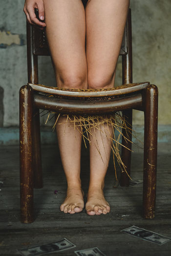 Low section of woman standing in broken chair