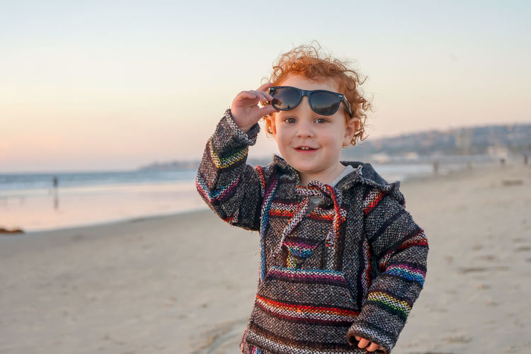 Portrait of smiling boy standing on beach against sky during sunset